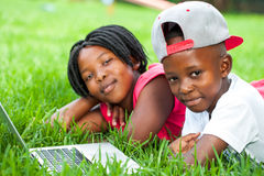 African kids laying on grass with laptop. Close up portrait of African boy and girl laying on green grass with laptop royalty free stock photos