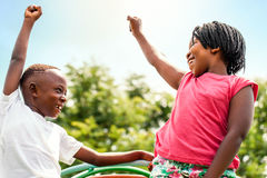 African kids looking at each other raising hands. Close up portrait of two happy African kids looking at each other raising hands outdoors stock photo