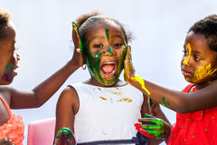 African kids painting friends face. Portrait of African kids painting themselves with color paint.Isolated against light background royalty free stock image