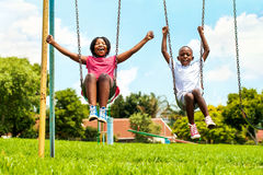 African kids playing on swing in neighborhood. Action portrait of shouting African kids playing on swing in neighborhood.Out of focus houses in background Stock Photography