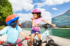 African kids riding bikes along a river embankment royalty free stock photo