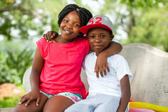 African kids sitting together on bench. Close up portrait of two African kids sitting together on bench in park royalty free stock photos