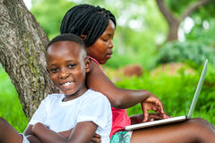 African kids under tree with laptop. Close up portrait of happy African kids under tree playing on laptop stock photo