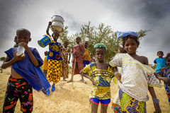 African kids walking in the countryside, Mali. Unidentified kids walking in the countryside, a young girl is carrying kitchenware on her head, pure African royalty free stock photo
