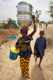 African kids walking in the countryside, a young girl is carrying kitchenware on her head. MOPTI, MALI, DECEMBER 31: Unidentified kids walking in the countryside royalty free stock photography