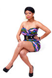 African lady. Elegant african lady in full length seated pose royalty free stock image