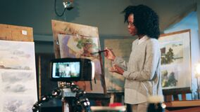 African ethnicity lady is holding an art lesson and recording it. Creation, inspiration concept.