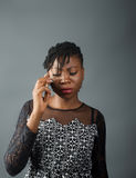 African lady looking pensive whilst on a call stock photography