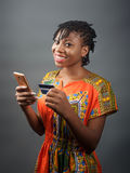 An african lady making an online payment with a debit card. An portrait shot of a lady making an online payment using a debit card Royalty Free Stock Image