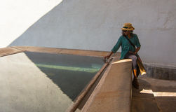 African Lady at pool. An African Lady contemplates the still waters of an antique laundry pool at the spanish town of Caldes de Montbui stock photo