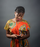 An african lady sending a message on her mobile phone. A portrait shot of an african lady interfacing with her mobile phone Stock Photos