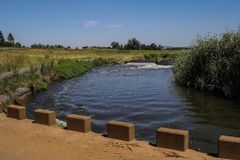 African landscape with a river, a bridge and a weir. African landscape with a low-water bridge, a river and a weir with a clear blue sky, image in landscape Royalty Free Stock Images