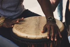 An African or Latin brown djembe conga drum being played against stock photos