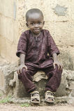 African little black boy sitting outdoors with a light smile. Little african boy sitting on stone and looking at camera with blurred background Royalty Free Stock Image