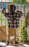 African little boy standing, small kids playing. In Africa. Children portraits on the street stock photography