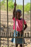 African little child standing near fence royalty free stock photo