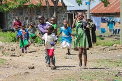 African little children coming from school. African little school children boys and girls play on the street in the small village school on a playground outside royalty free stock photos