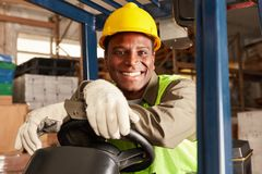 African logistics man as a forklift driver stock photo