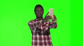 African make selfie on green screen. African young man make selfie using smartphone on green screen stock footage