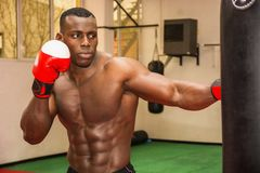 African male boxer punching ball wearing boxing Stock Image