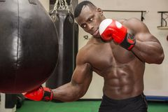 African male boxer punching ball wearing boxing. African black male boxer punching ball wearing boxing gloves in gym royalty free stock images