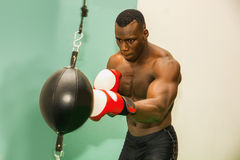 African male boxer punching ball wearing boxing gloves Stock Images