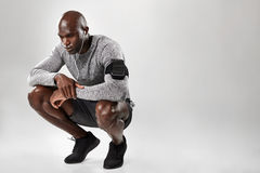 African male model crouching on grey background Stock Photography