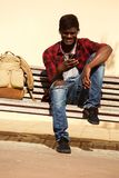 African male model sitting on bench using cell phone. Portrait of african male model sitting on bench using cell phone Stock Image