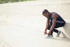 African male runner tying his shoe on steps. Young black man runner tying his shoelaces Royalty Free Stock Photos