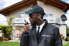 African Male Security Guard Talking On Walkie Talkie. Young African Male Security Guard Talking On Walkie Talkie In Front Of House royalty free stock images