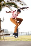 African male skateboarder doing tricks outside Royalty Free Stock Photo