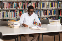 African Male Student In A Library. Portrait Of African Clever Student With Open Book Reading It In College Library - Shallow Depth Of Field Stock Photography