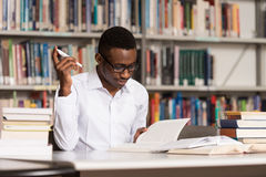 African Male Student In A Library. Portrait Of African Clever Student With Open Book Reading It In College Library - Shallow Depth Of Field Royalty Free Stock Photo