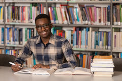 African Male Student In A Library. Portrait Of African Clever Student With Open Book Reading It In College Library - Shallow Depth Of Field Stock Photo