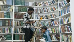African male student searching books from the shelves while standing on ladder in university library for african female. African male student searching books stock footage