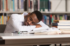 African Male Student Sleeping In Library. Sleeping African Student Sitting And Leaning On Pile Of Books In College - Shallow Depth Of Field Royalty Free Stock Photography