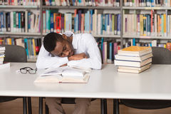 African Male Student Sleeping In Library. Sleeping African Student Sitting And Leaning On Pile Of Books In College - Shallow Depth Of Field Royalty Free Stock Images
