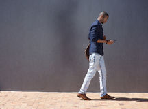 African male student walking with tablet. Side portrait of african male student walking with tablet Royalty Free Stock Image