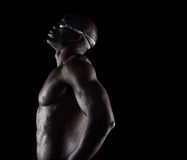 African male swimmer taking a break. Side view of african male swimmer taking a break. Muscular young man on black background with copy space Royalty Free Stock Images