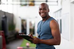 African male trainer clipboard. Handsome african american male trainer with clipboard Royalty Free Stock Image