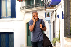 African male traveler talking on cellphone. Portrait of african male traveler talking on cellphone Royalty Free Stock Images