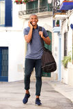 African male traveler talking on mobile phone. Full length portrait of happy young african male traveler with bag talking on mobile phone Stock Photography