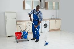 African Male Worker Cleaning Floor With Mop Royalty Free Stock Image