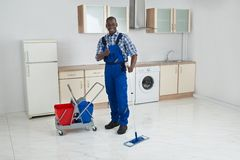 African Male Worker Cleaning Floor With Mop. Young Happy African Male Worker Cleaning Floor With Mop Stock Photography