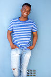 African male youth smiling against blue wall. Portrait of african male youth smiling against blue wall Stock Photos