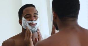 African man applying shaving foam on face looking in mirror