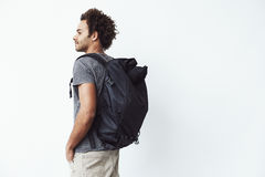 African man with backpack standing back to camera looking in side. White background. Young african man with backpack standing back to camera looking in side Stock Photos