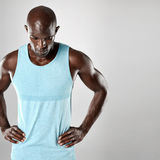 African man with bald head and muscular arms. Handsome young african man with bald head and muscular arms looking downward over grey background Royalty Free Stock Image