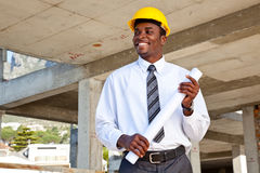 African man in building site. African man in a construction site wearing a hard hat and holding building plans Royalty Free Stock Photos