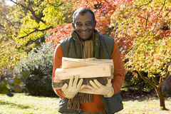 African man carrying firewood in autumn Stock Photography